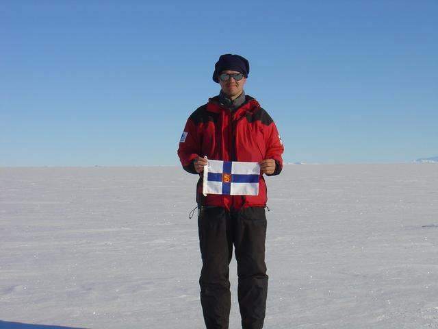 Me with flag of Finland and part of Heimefrontfjella at horizon