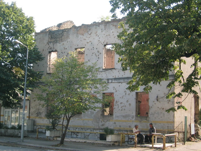 Life goes on: Men converse in front of bullet-holed building in Mostar