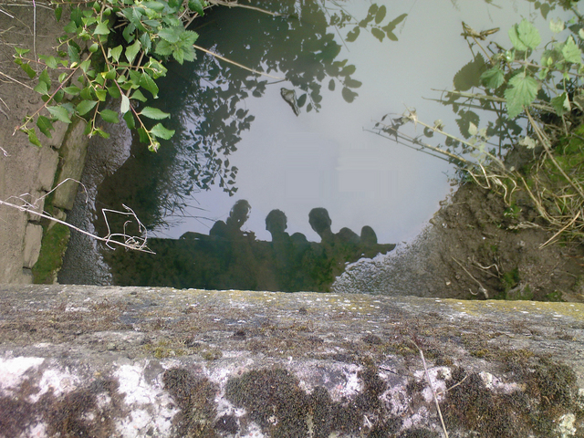 Corine, Adriaan and Bert reflected in a small river. (From a bridge)