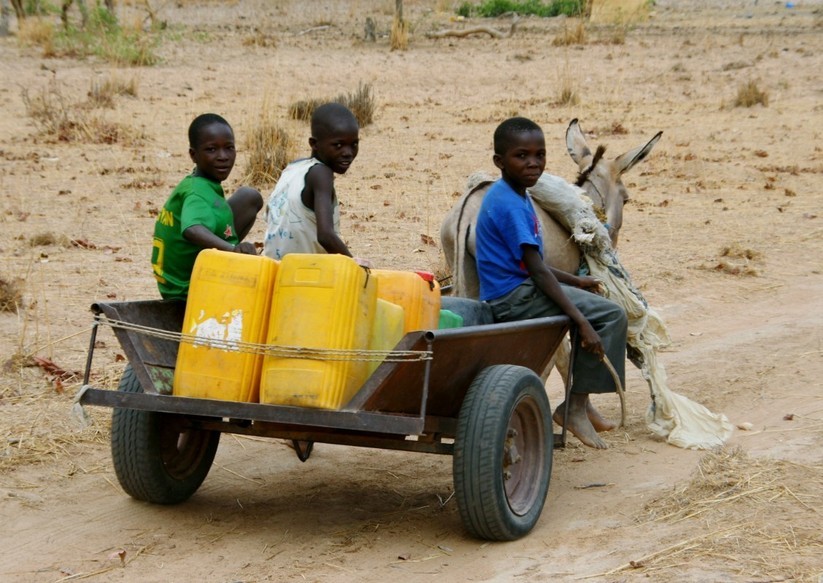 Kids transporting water cans