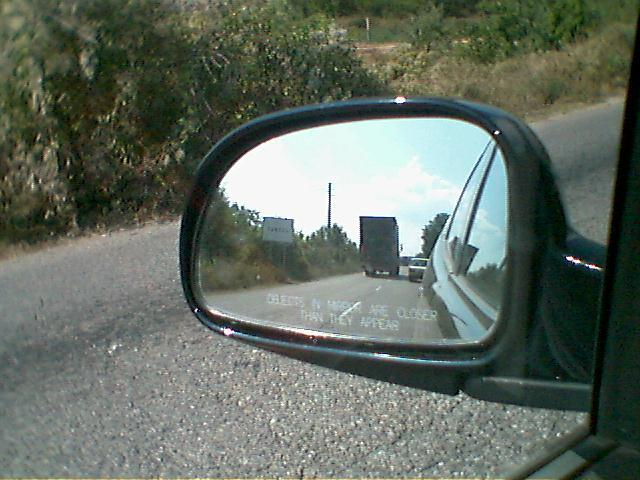 In the rear-view-mirror the exit for the village is seen