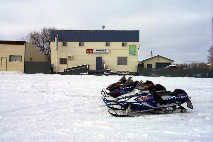 Snowmobiles parked at Ronnie's Tavern and Confectionery in Macdowell.