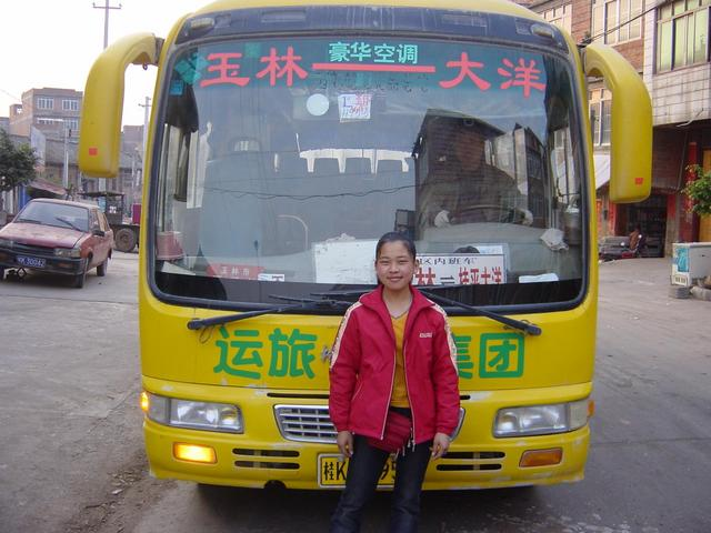 17-year-old ticket seller in front of bright yellow Yulin-to-Dayang bus.