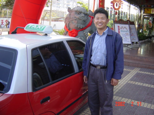 The taxi driver who took me from Zhangzhou to Longyan, outside the entrance to the Houston Hotel