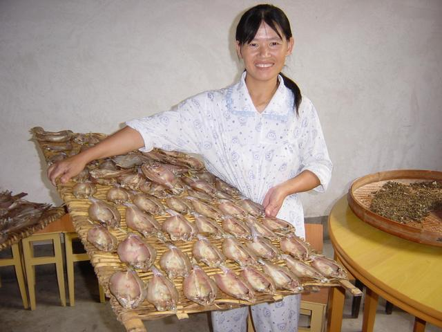 Pyjama-clad guesthouse proprietress proudly displaying dried fish