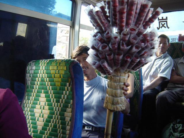 Bus passenger with pole of candied crab apples on bamboo skewers