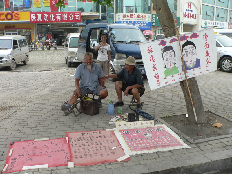 Ah Feng standing behind a couple of roadside fortune-tellers in Hézé