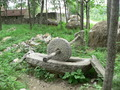 #3: Millstone, with a stone house and wall in the background