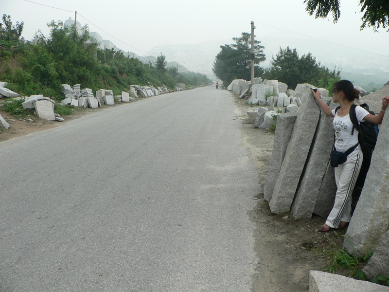 Ah Feng amid the slabs of rock littering the side of the road