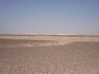 #1: View of general area taken from asphalt road looking in a NNW direction. Confluence lies approx. 8 km towards left of image