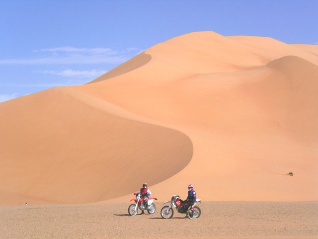 Two bikers against the sand dunes toward east