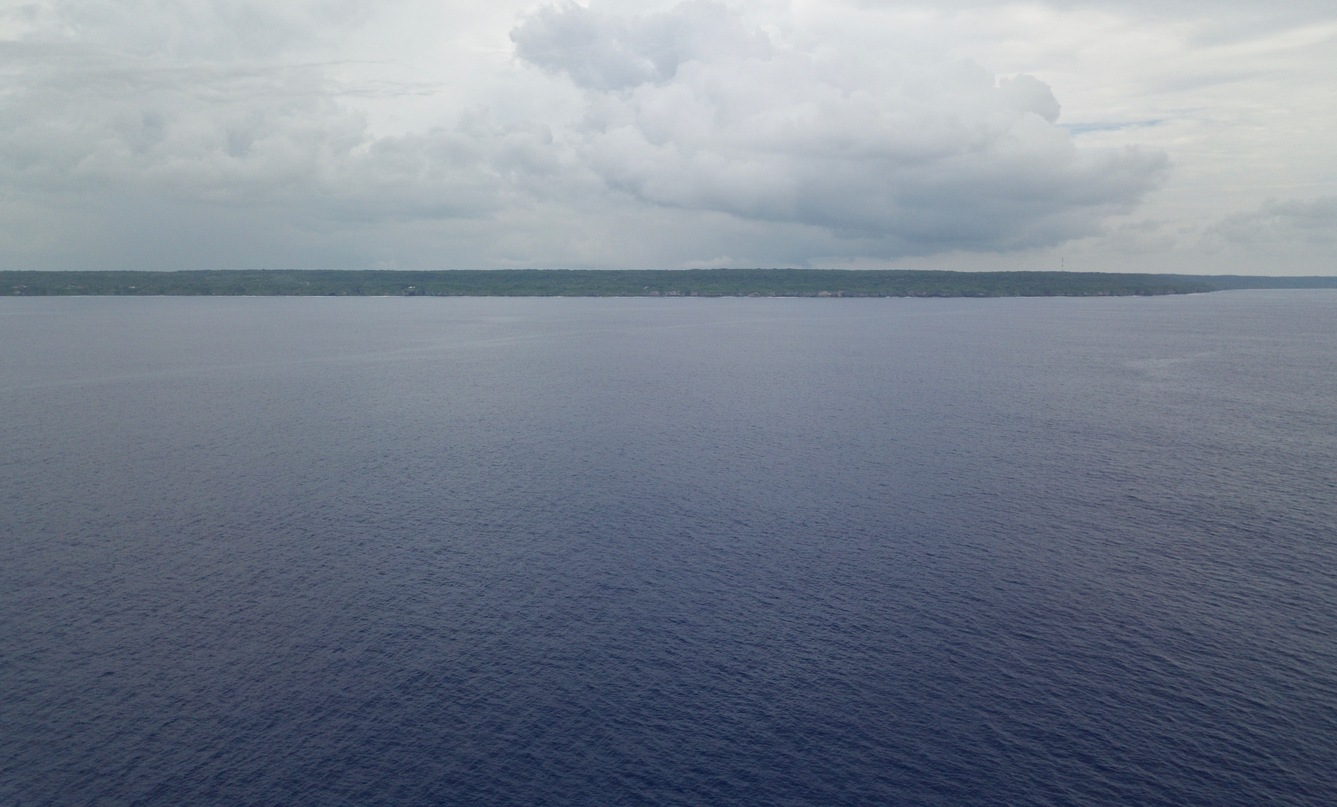 A drone's eye view of Niue from 18.9839°S 169.9375°W, at ~50 m above the ocean. The confluence point is about 7 km farther away than this, but a shipboard view from the point might be similar.