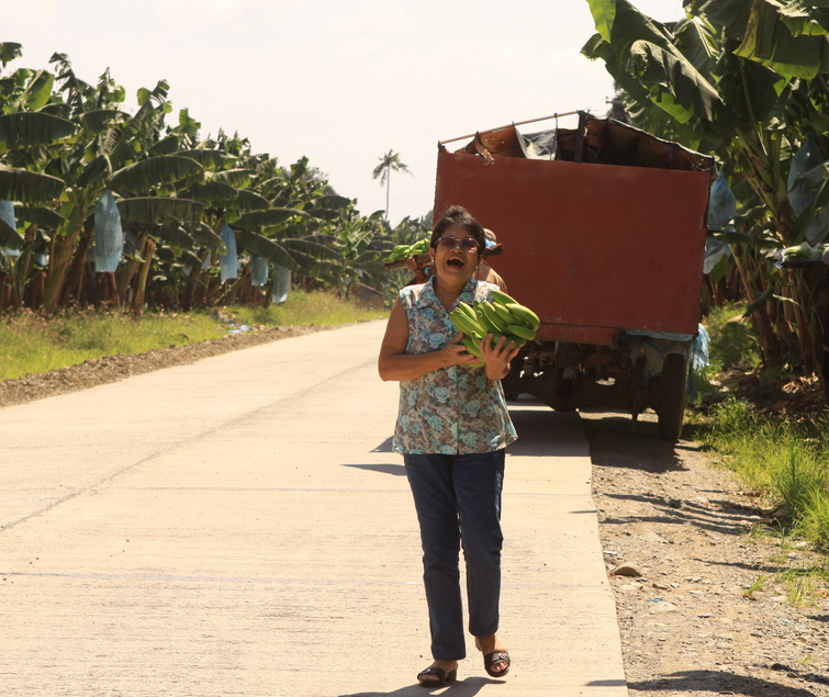 Santah with a bunch of Cavendish given by man harvesting banana  at Sto. Tomas, Davao del Norte