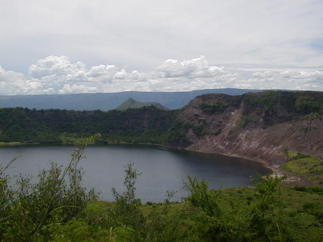View looking NE from rim of Binitiang Malaki volcano lake, the largest on the island. Last erupted in 1715. Steam could be seen escaping from vents on the right side of the shore (scorched area).