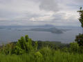 #3: The confluence sits on the backside of Volcano Island (center of photo) in Taal Lake. View is SSE from the town of Tagatay on the northern rim of the pre-historic Taal Volcano. The Southern rim and Mt. Maculot (shrouded in clouds) are in the background.