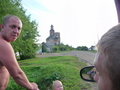 #7: Pavel grimacing at Evgeny explaining the confluence concept to him. View of hamlet, dilapidated cathedral and our white jeep Niva in the background.