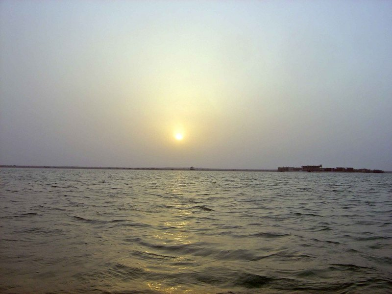 View of the confluence site, looking west towards the setting sun;  The shore and fenced-in beach camp dwellings are 288 m west of 26N 50E.