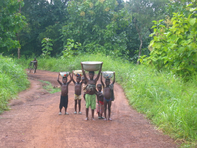 Girl carrying 20 litres of water and her brother