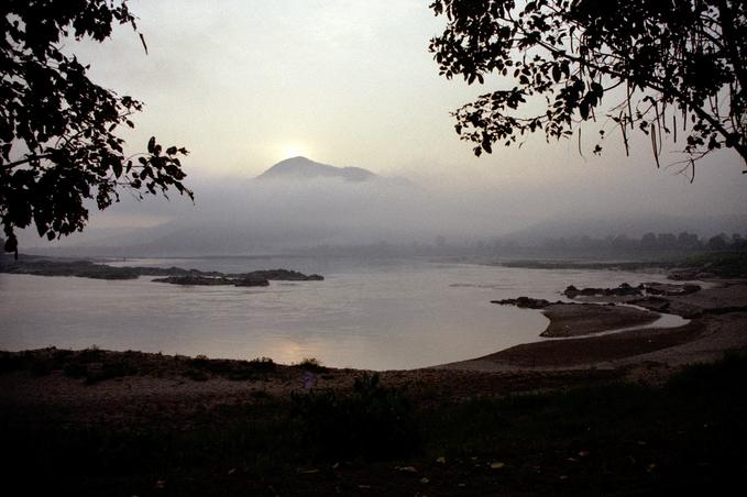 Sun rising over moutain; Mekong rapids in foreground