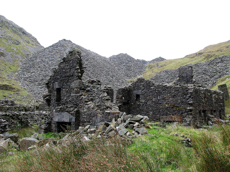 Quarrymen's row house ruins with some of the many slate waste heaps in the background.