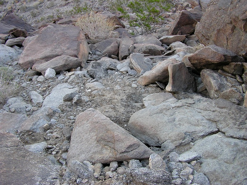 The confluence point lies on this steep, rocky hillside, about 1000' above the surrounding desert