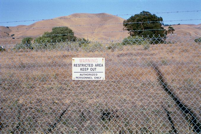 The confluence is located 168 feet beyond this security fence - probably close to the oak tree on the right