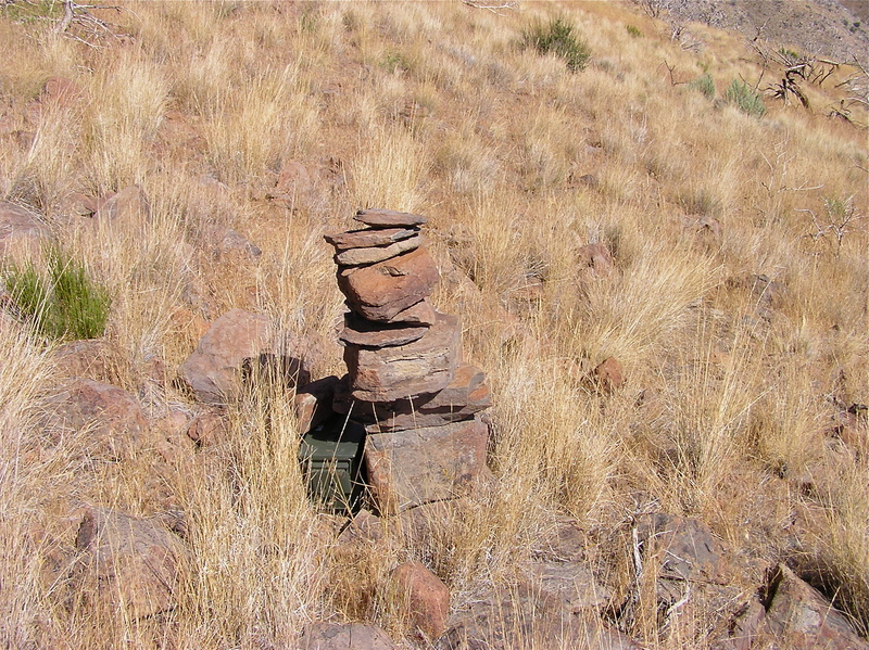 The confluence point lies near this rock cairn (and geocache), near the top of a rocky, grassy hillside