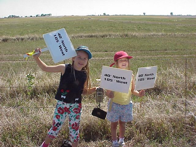 Young confluence hunters jubilantly display signs and GPS as site is found.
