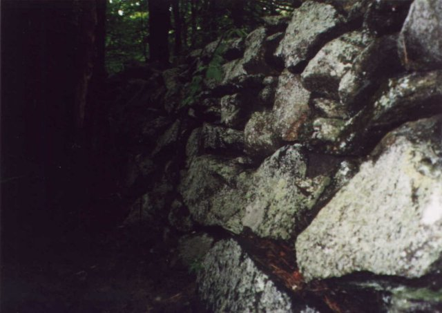 A tall stone wall at the confluence.