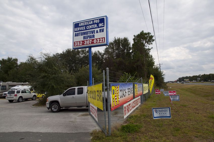 A front-on view of the RV repair shop (with the confluence point at the left).  Just days from the 2012 presidential election, there are lots of Mitt Romney supporters in this part of Florida.