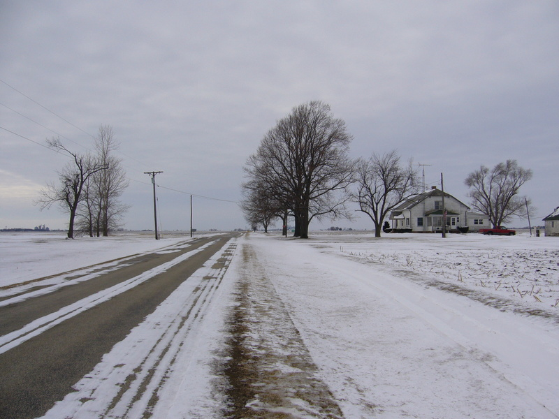 West: road, field and house