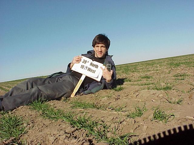 Joseph Kerski lying in the field at the confluence site.