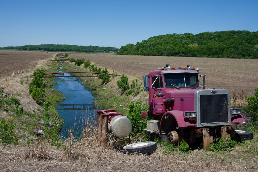 The engine of this truck is apparently being used to run a pump for this irrigation canal