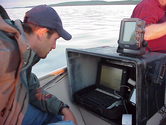 Ryan Krapp, left, monitors Trimble GPS and Garmin Sonar equipment used to map the floor of Devils Lake, North Dakota.