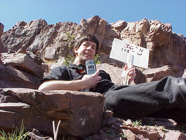 Geographer Joseph Kerski with sign at the confluence.