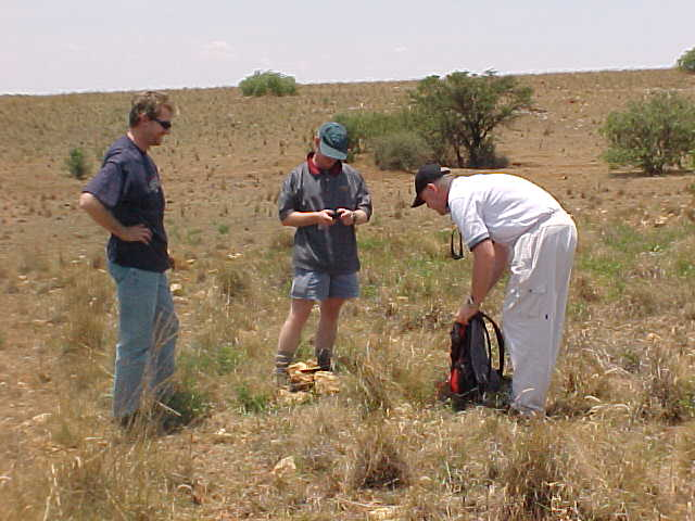 Henning, Roland and Barry use rocks in the area to build a small cairn on the point of 26S 26E